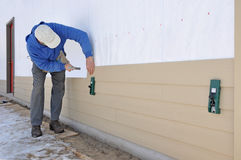 Man installing siding using gauges. Man installing cement fiber siding using gauges royalty free stock images