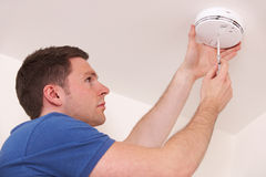 Free Man Installing Smoke Or Carbon Monoxide Detector Stock Image - 63303141