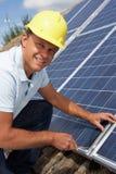Man installing solar panels. Smiling at camera Stock Photos
