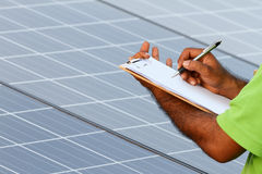Man installing solar panels. And writing Stock Photography