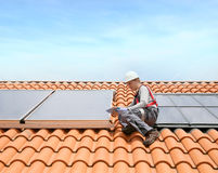 Man installing solar panels on roof Stock Photos