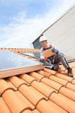 Man installing solar panels on roof Stock Photography
