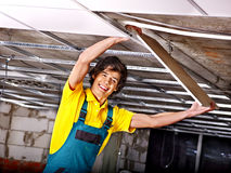 Man installing suspended ceiling. Man in builder uniform installing suspended ceiling Stock Image