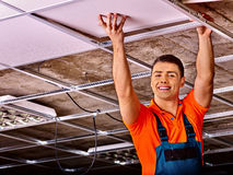 Man installing suspended ceiling. Man in builder uniform hand up  installing suspended ceiling Stock Image