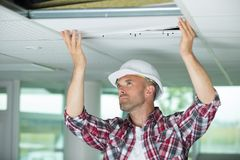 Man installing suspended ceiling in house. Man stock photography