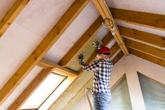 Man installing thermal roof insulation layer - using mineral woo Stock Images