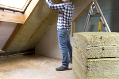 Man installing thermal roof insulation layer - using mineral woo. L panels. Attic renovation and insulation concept stock image