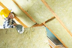 Man installing thermal roof insulation layer - using mineral woo. L panels. Attic renovation and insulation concept stock photography