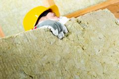 Man installing thermal roof insulation layer - using mineral woo royalty free stock photos