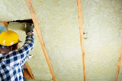 Man installing thermal roof insulation layer - using mineral woo. L panels. Attic renovation and insulation concept royalty free stock photos