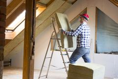 Man installing thermal roof insulation layer - using mineral woo Stock Photo