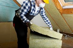 Man installing thermal roof insulation layer - using mineral woo royalty free stock image