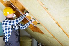 Man installing thermal roof insulation layer - using mineral woo. L panels. Attic renovation and insulation concept royalty free stock image