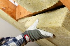 Man installing thermal roof insulation layer - using mineral woo. L panels. Attic renovation and insulation concept royalty free stock images