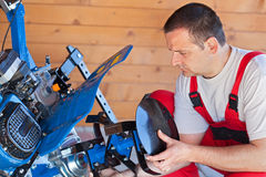 Man installing tilling accessory on agricultural machine Royalty Free Stock Image