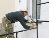 Man installing windowsill #3. A worker installing a windowsill using a construction foam royalty free stock image