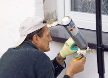 Man installing windowsill #4. A worker installing a windowsill using a construction foam royalty free stock image