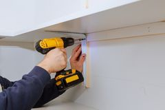 Man installing wooden shelves on brackets wall installing a shelf. Man installing wooden shelves on brackets installation of shelves Royalty Free Stock Photography