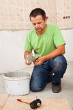 Man installs ceramic floor tiles - preparing the adhesive Royalty Free Stock Images