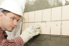 Man installs ceramic tile Royalty Free Stock Photos