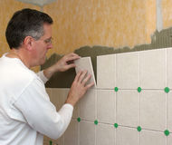 Man installs ceramic tile
