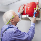 Man installs fire extinguisher Stock Image