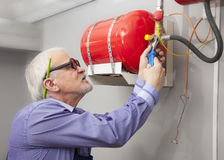 Man installs fire extinguisher Royalty Free Stock Photo