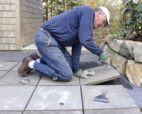 Man installs flagstone on patio stock photo