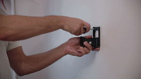 Man installs the holder bracket  on the wall. Man installs the holder bracket for the TV on the wall stock video footage