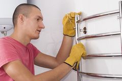 Man installs towel dryer. Man installs an electric heated towel rail in the bathroom stock photography