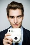 Man with instant camera Stock Image