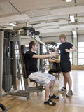 Man instructing how to use an exercise machine Stock Image