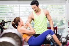 Man instructor advising Asian woman doing sit-ups Stock Images