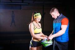 Man instruktör- och kvinnaidrottshallhjälp för att smörja händer med talk, magnesium royaltyfri fotografi