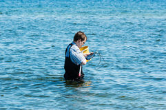 Man with instrument in water Stock Photography