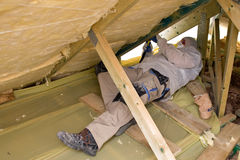 Man insulating a roof. Man in protective clothing insulating a roof with ceramic wool and working in a restricted space stock photography