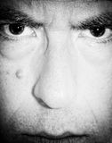 Man with intense eyes. Full frame close-up of a man's face with an intense expression in his eyes Royalty Free Stock Images