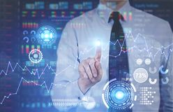 Glowing infographics and HUD, businessman. Man interacting with a blue and orange HUD. A blurred interface background. Concept of the future and technologies Royalty Free Stock Photography