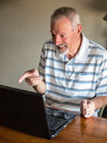 Man interacting with computer. Senior is having fun at his computer Stock Image