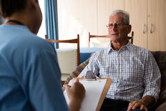 Man interacting with female doctor writing on paper in nursing home Stock Photo