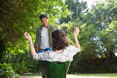 Man interacting with woman while pushing wheelbarrow in garden. Man interacting with women while pushing wheelbarrow in garden on a sunny day Royalty Free Stock Photos