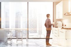 Man in panoramic kitchen with cityscape stock image