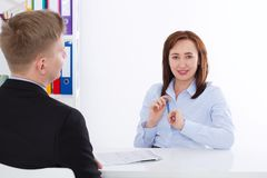 Man is interviewed at office background. Businesswoman and businessman have meeting and conversation. Copy space and mock up. Selective focus Royalty Free Stock Image