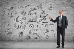 Man introduce plan. Asian business man introduce plan on the wall in a room Royalty Free Stock Photos