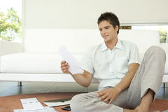 Man with Invoices Sitting on Floor. Young man working on his finances, sitting on the floor by the sofa Stock Photo