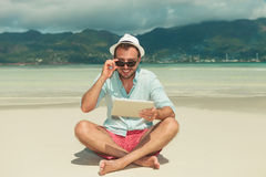 Man with ipad on the beach smiling and fixing his sunglasses Stock Photography