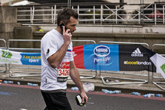 Man on iPhone while running the maratrhon Stock Image