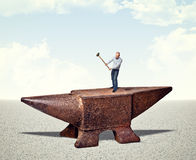 Man on iron anvil Royalty Free Stock Photos