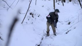 Exhausted soldier walks through a snowy forest stock footage