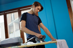 Man with iron doing chores Stock Photos